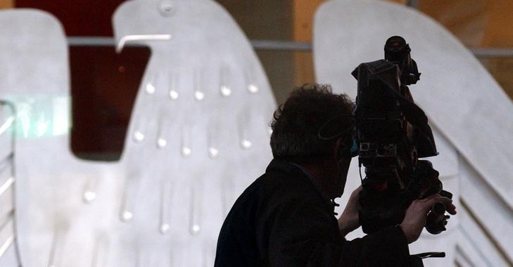 Silhouette eines Kameramanns mit Kamera vor dem Bundesadler im Plenarsaal des Bundestages © DBT/Hans-Günther Oed