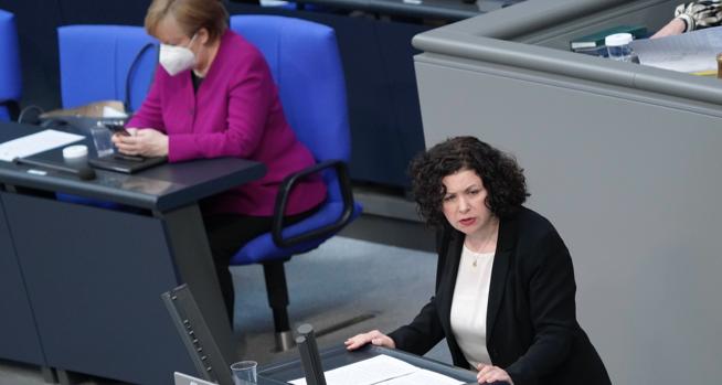 Amira Mohamed Ali am Rednerpult des Bundestages, dahinter Bundeskanzlerin Merkel auf der Regierungsbank schaut auf ihr Handy © picture alliance/Flashpic/Jens Krick