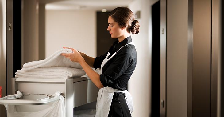 Zimmermädchen an einem Wäschewagen in einem Hotelflur | Foto: © iStockphoto.com/STEFANOLUNARDI