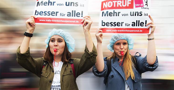 """Berliner Pflegekräfte beim Pflegestreik der Charité halten Schilder hoch mit dem Slogan """"Mehr von uns ist besser für alle!"""""""