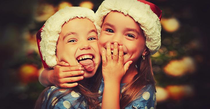Lachende Kinder mit Weihnachtsmannmützen umarmen einander.  Foto: © istock.com/evgenyatamanenko