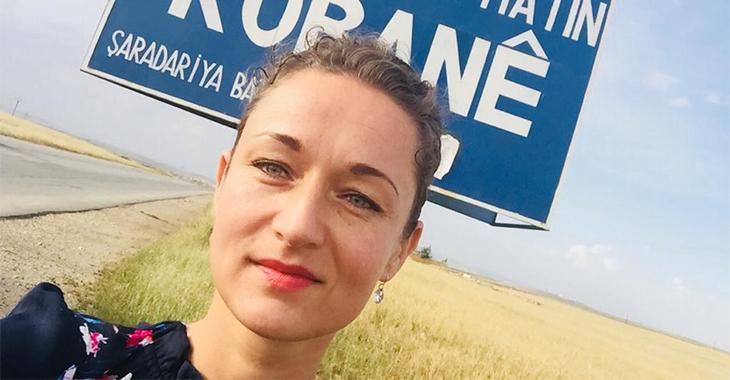Zaklin Nastic vor dem Ortseingangsschild von Kobane