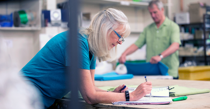 Eine Frau beugt sich über Papiere ©iStock/DGLimages