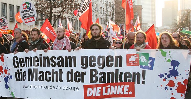 """Demonstrierende bei der Blockupy-Kundgebung im März 2015 in Frankfurt/Main; Transparent von """"DIE LINKE"""" mit der Aufschrift """"Gemeinsam gegen die Macht der Banken"""""""