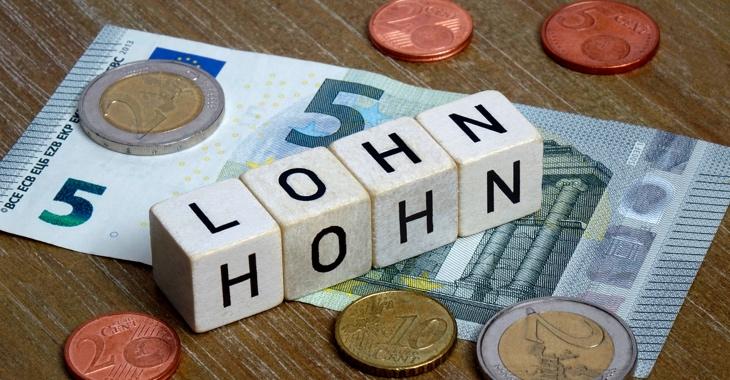 Auf einem Fünf-Euro-Schein stehen Würfel mit den Worten Lohn und Hohn © picture alliance/dpa-Zentralbild