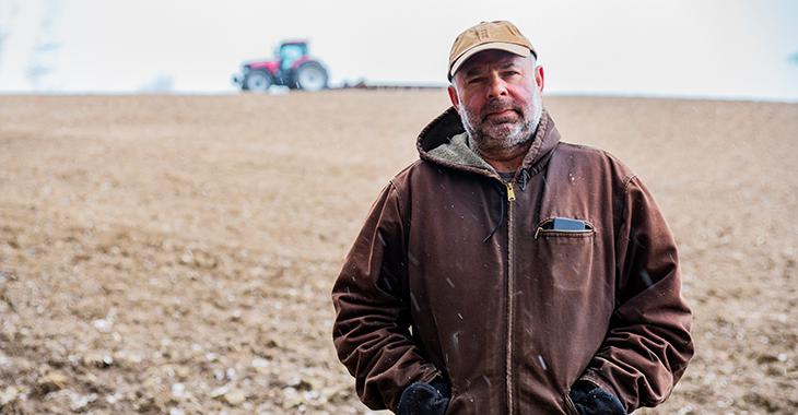 Ein Landwirt steht auf einem winterlichen Acker, über den unscharf im Hintergrund ein Traktor mit Arbeitsgerät fährt. Foto: © istock.com/Fertnig
