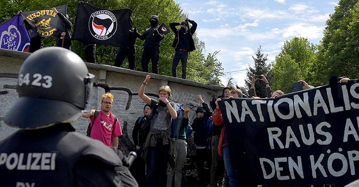 Antifa-Demonstranten halten Fahnen hoch, ein Polizist mit Helm steht ihnen gegenüber