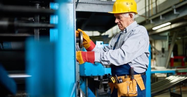 Ein älterer Arbeiter mit gelbem Schutzhelm schraubt an einer blauen Maschinen © iStock/SeventyFour