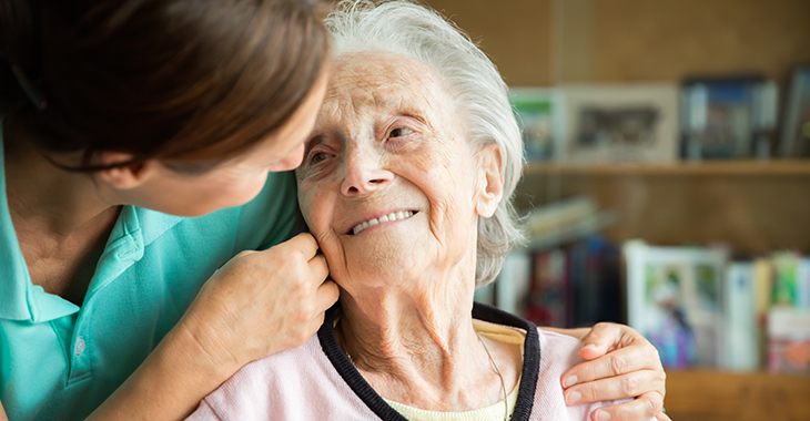 Eine ältere Dame schaut freundlich zu einer Pflegerin, die ihr die Wange streichelt. Foto: © istock.com/FredFroese