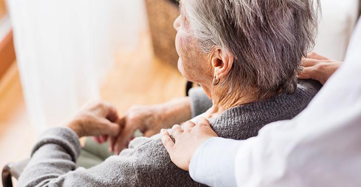 Alte Frau im Rollstuhl mit Pflegerin