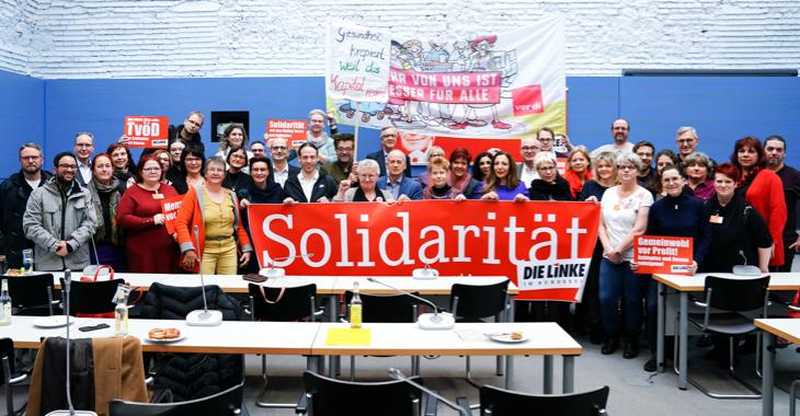 Mitarbeiter/inn der Ameos- und Asklepios-Kliniken und Mitglieder der Linksfraktion halten ein Transparent mit der Aufschrift Solidarität