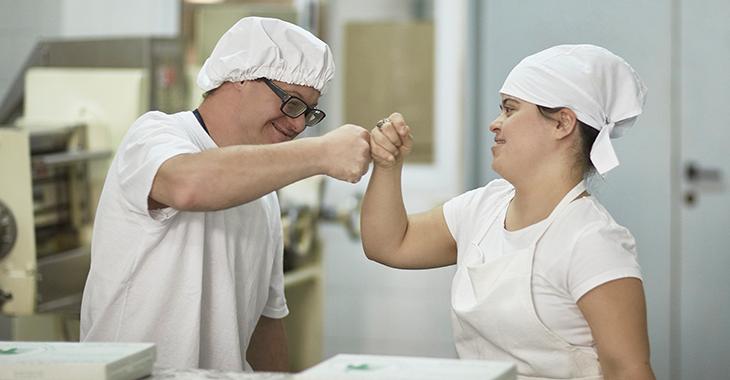 Zwei Menschen mit Behinderung tragen weiße Arbeitskleidung und freuen sich gemeinsam über ihren Arbeitserfolg in einer Pasta-Werkstatt. Foto: © istock.com/xavierarnau