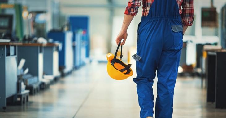Ein Arbeit in blauer Latzhose und mit gelbem Helm in der Hand läuft durch eine Werkhalle © iStock/gilaxia