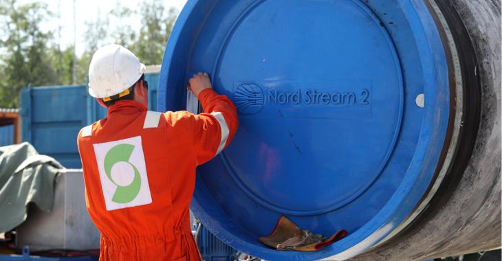 Ein Arbeiter vor einem Rohr mit blauem Verschluss und der Aufschrift Nord Stream 2 © Alexander Demianchuk/TASS/ddp/Sipa USA