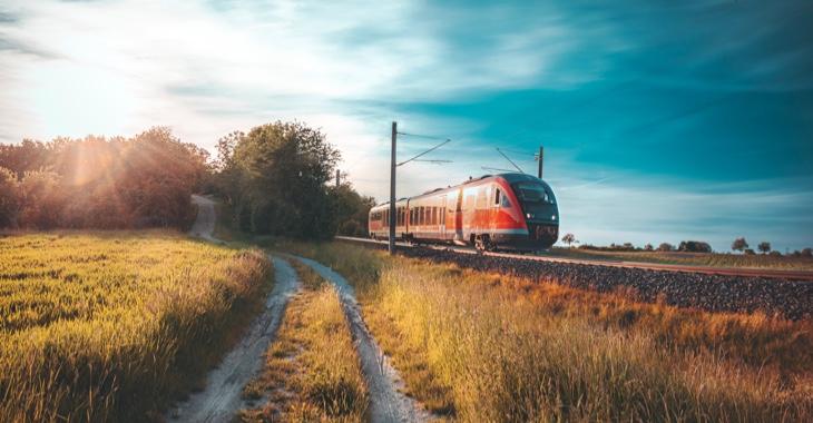 Ein Feldweg neben einem Bahngleis mit einem Regionalexpress der Bahn © iStock/Say-Cheese