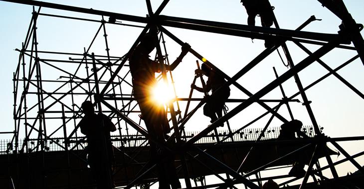 Silhouetten von Bauarbeitern, die auf einer Baustelle Gerüste montieren © iStockphoto.com/hxdbzxy