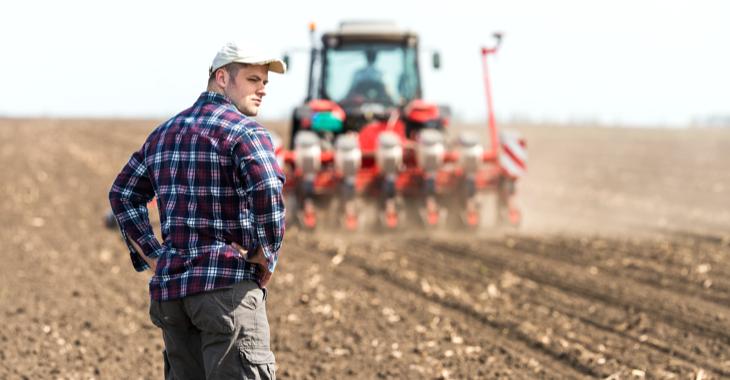 Junger Bauer auf einem Acker hinter einem Traktor bei der Aussaat © iStock/fotokostic
