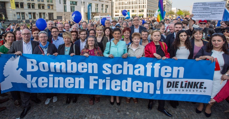 Bei der Friedenskundgebung am 18. April 2018 am Brandenburger Tor in Berlin für Deeskalation in Syrien halten Mitglieder der Linksfraktion ein Transparent mit der Aufschrift: Bomben schaffen keinen Frieden!