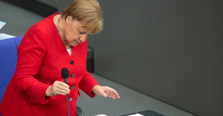 Bundeskanzlerin Angela Merkel hält ein Mikrofon auf der Regierungsbank im Plenarsaal des Bundestages © Ralf Hirschberger/dpa-Zentralbild/dpa