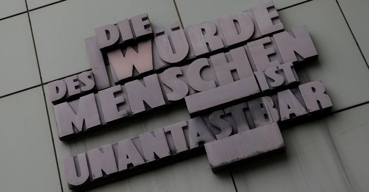 """Das Grundgesetz-Zitat """"Die Würde des Menschen ist unantastbar"""" an der Fassade eines Gerichtsgebäudes in Frankfurt am Main  © Arne Dedert/dpa"""