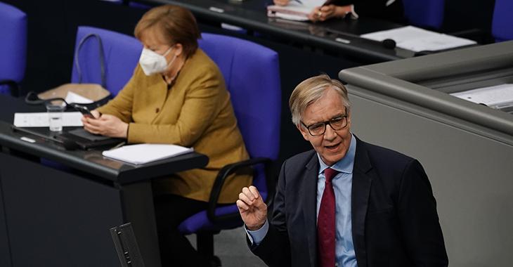 Dietmar Bartsch im Plenum mit Angela Merkel im Hintergrund