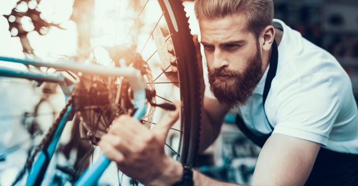 Ein Mechaniker repariert ein Fahrrad © iStock/vadimguzhva