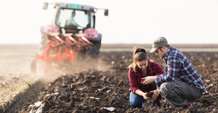 Eine Bäuerin und ein Bauer vor einem Traktor mit Pflug auf einem umgepflügten © FeldiStock/fotokostic