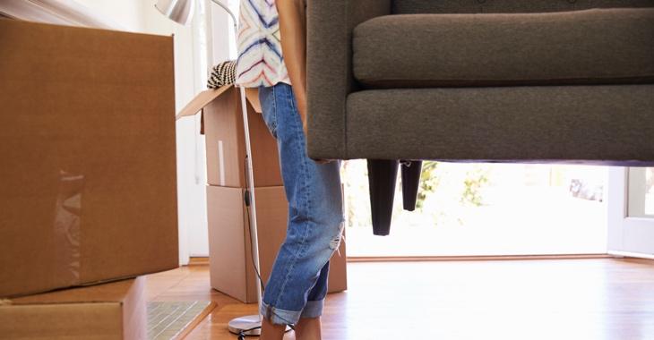 Eine Frau in Jeans trägt ein Sofa © iStockphoto.com/monkeybusinessimages