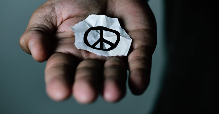Das CND-Friedenssymbol auf einem abgerissenen Papier in einer aufgehaltenen Hand © iStockphoto.com/nito100