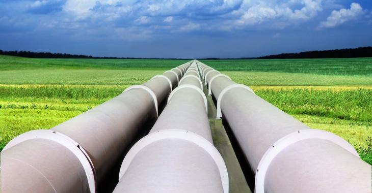 Eine Gaspipeline mit drei riesigen Röhren führt über ein grünes Feld © iStockphoto.com/suaphoto