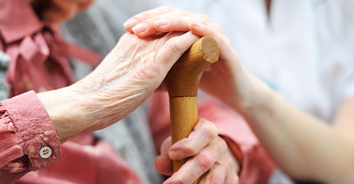 Hand einer Frau auf der Hand einer älteren Frau mit einem Gehstock