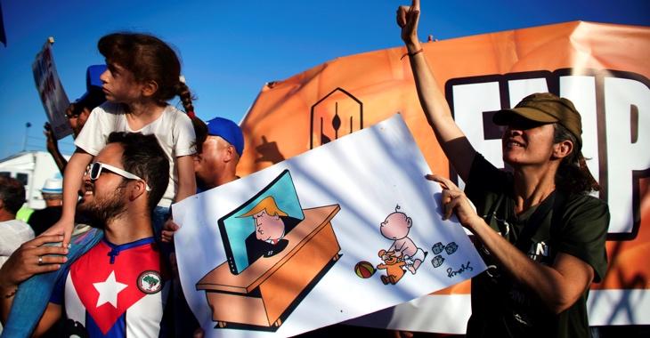Bei der 1.Mai-Demo 2019 in Kubas Hauptstadt Havanna halten Teilnehmer eine Zeichnung, auf dem ein Kleinkind seinem Spielzeugbär die Augen zuhält, damit er Donald Trump nicht im Fernsehen sehen muss ©REUTERS/Alexandre Meneghini