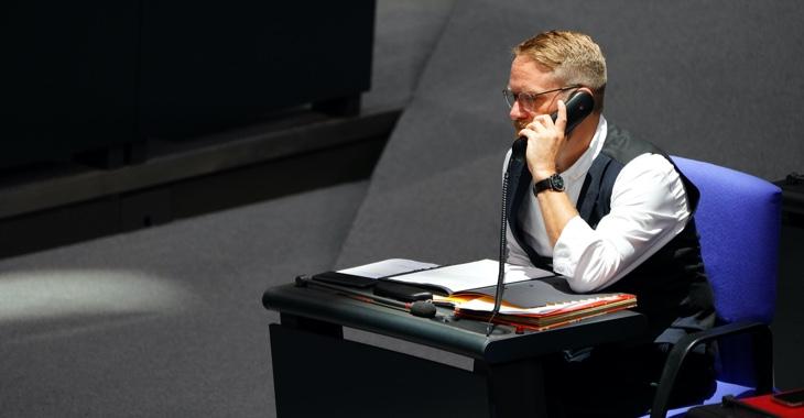 Jan Korte telefoniert an seinem Platz im Plenarsaal des Bundestages