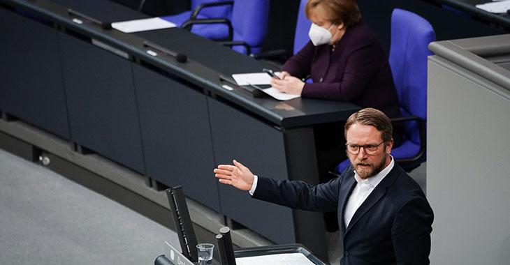 Jan Korte spricht im Plenum mit Angela Merkel im Hintergrund