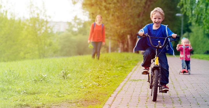 Eine Mutter mit ihrem Sohn auf einem Fahrrad und ihrer Tochter auf einem Tretroller © iStockphoto.com/Nadezhda1906