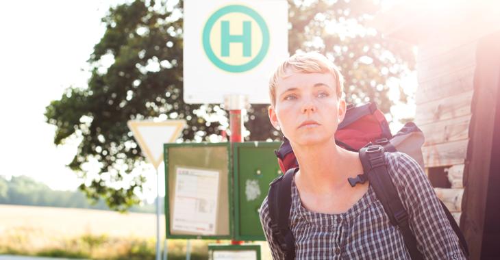 Eine junge Frau mit Rucksack an einer Bushaltestelle ©iStock/lowkick