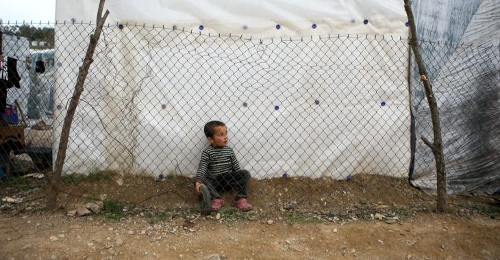 Ein Flüchtlingsjunge sitzt hinter einem Gitterzaun im Lager Moria auf der griechischen Insel Lesbos © REUTERS/Elias Marcou