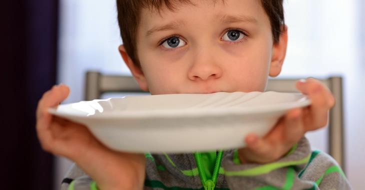 Ein Junge hält einen Teller vor seinen Mund © iStockphoto/djedzura