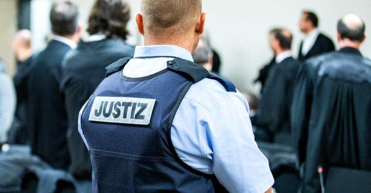 Ein Justizbeamter in einem Gerichtssaal trägt eine Schutzweste mit der Aufschrift Justiz © dpa/Marcel Kusch