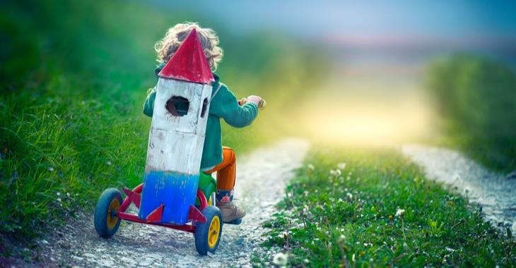Ein Kind fährt mit einem Dreirad auf einen Feldweg mit einer aus Pappe gebastelten Weltraum-Rakete auf den Rück geschnallt © iStock/oops7