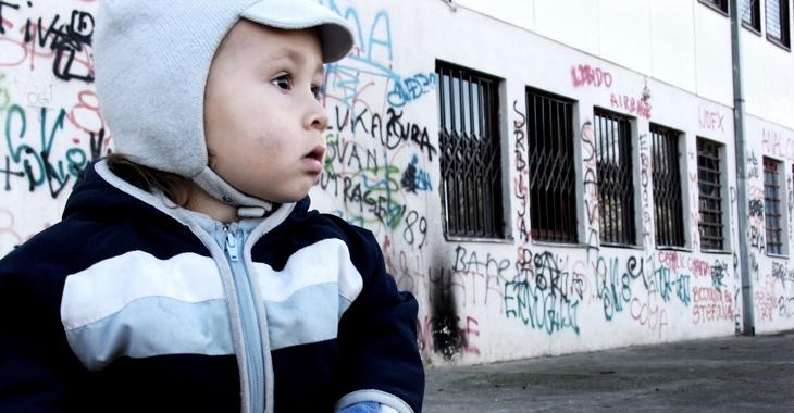 Ein Kind vor einem Haus mit Graffiti an der Wand und Gittern vor den Fenstern © iStock/brunette