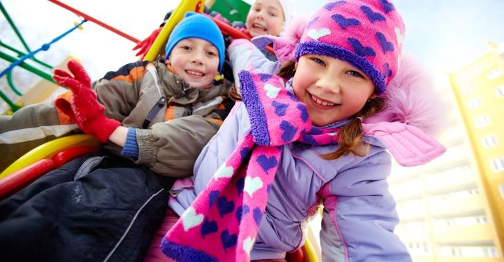 Drei Kinder im Winter auf einem Spielplatz © iStock/shironosov