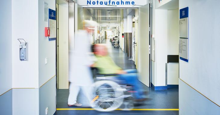 Ein Pfleger schiebt in einem Krankenhaus einen Patienten im Rollstuhl durch einen Flur mit einem Schild Notaufnahme an der Wand © iStock/upixa