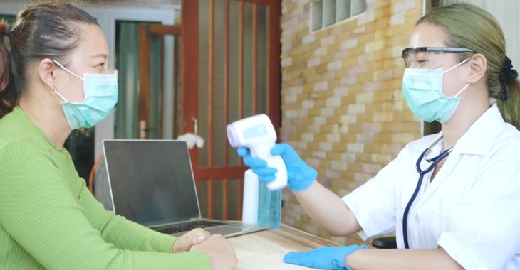 Patientin und Krankenschwester mit Gesichtsmaske und Fiebermessgerät