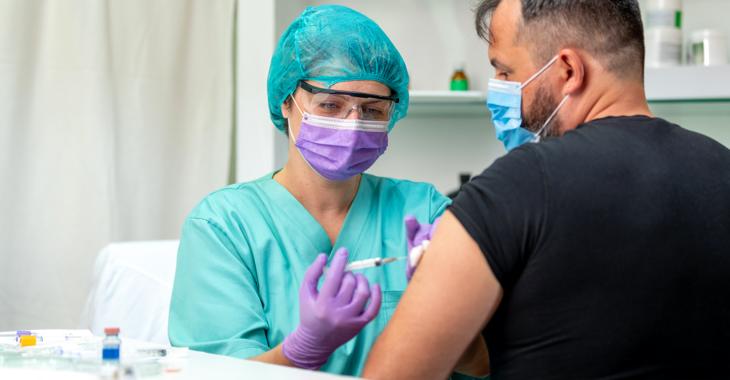 Krankenschwester mit Schutzbrille und Maske verabreicht einem Mann mit Maske eine Injektion @ iStock/zoranm