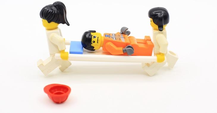 Lego-Figuren: Zwei Sanitäter tragen einen Patienten auf einer Trage © iStockphoto.com/LewisTsePuiLung