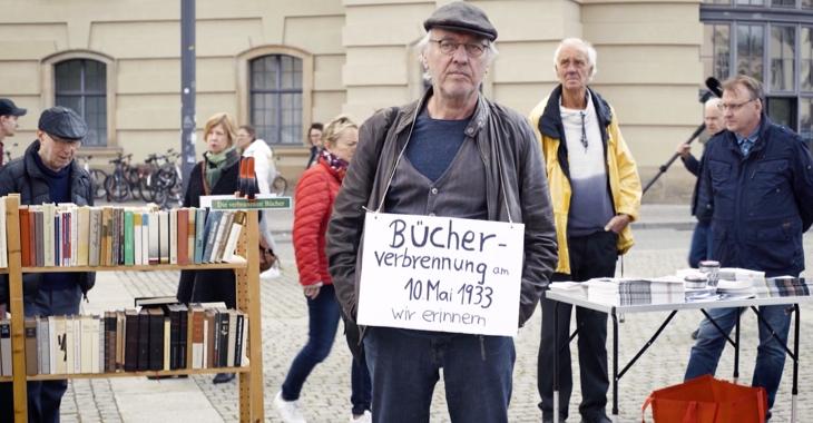 Beim »Lesen gegen das Vergessen« am 10. Mai 2019 auf dem Bebelplatz in Berlin hat ein Teilnehmer ein Schild umhängen mit Aufschrift »Bücherverbrennung am 10. Mai 1933. Wir erinnern.«