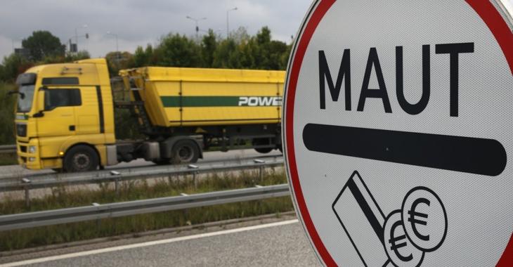 Ein gelber LKW fährt an einem Maut-Schild vorbei © Bernd Wüstneck/dpa