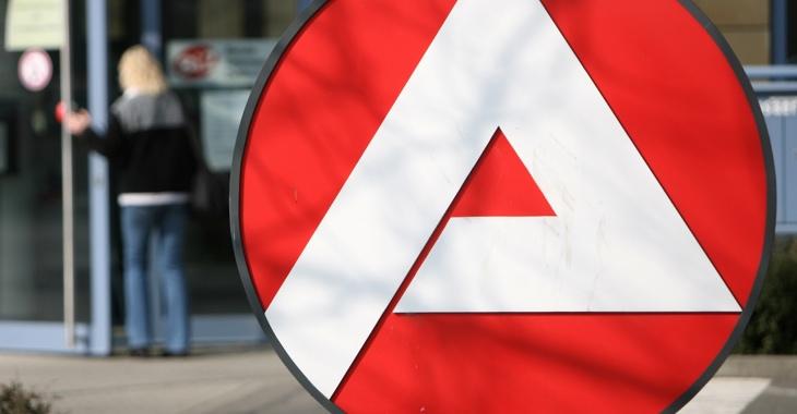 Logo der Agentur für Arbeit, dahinter verschwommen: eine Frau am Eingang eines Jobcenters © ddp images