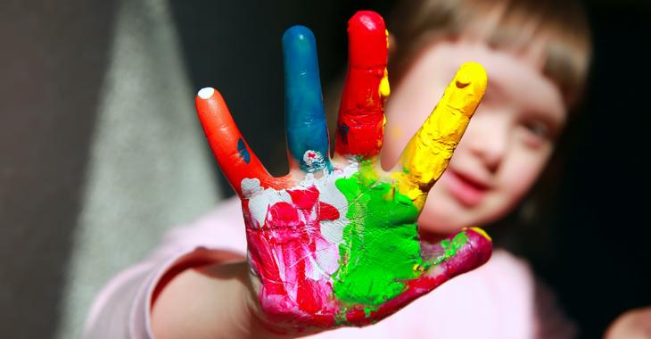 Mädchen mit Down-Syndrom hält ihre rechte Hand voller Farbe in die Kamera